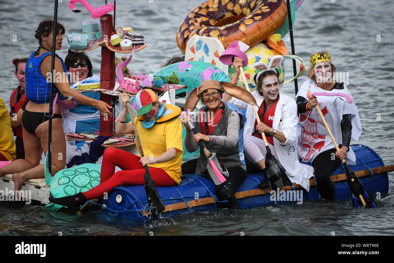 Swansea, Wales, UK. 11th August 2019. The Mumbles Raft Race, which is held every year off the coast of Mumbles near Swansea, Wales. The event, organised by the local RNLI, sees people in fancy dress, race their handmade rafts across a stretch of water whilst trying their best to keep afloat. It attracts hundreds of people to line to coastline to watch the antics, which raise over £15, 00 for the local RNLI charity each year. Credit: Robert Melen/Alamy Live News Stock Photo