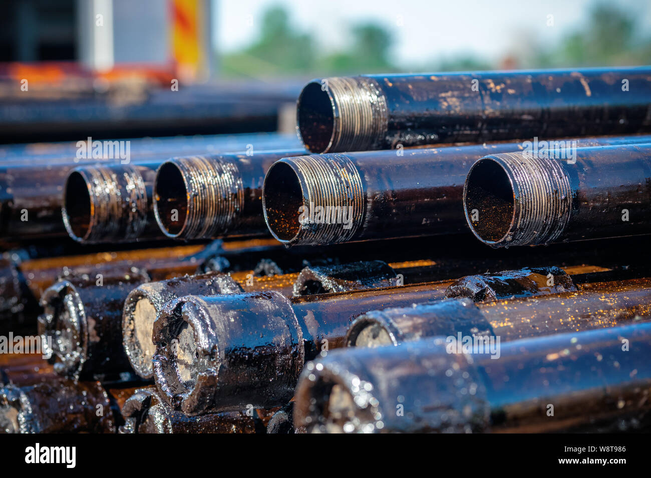 Oil Drill pipe. Rusty drill pipes were drilled in the well section. Downhole drilling rig. Laying the pipe on the deck. View of the shell of drill pip Stock Photo
