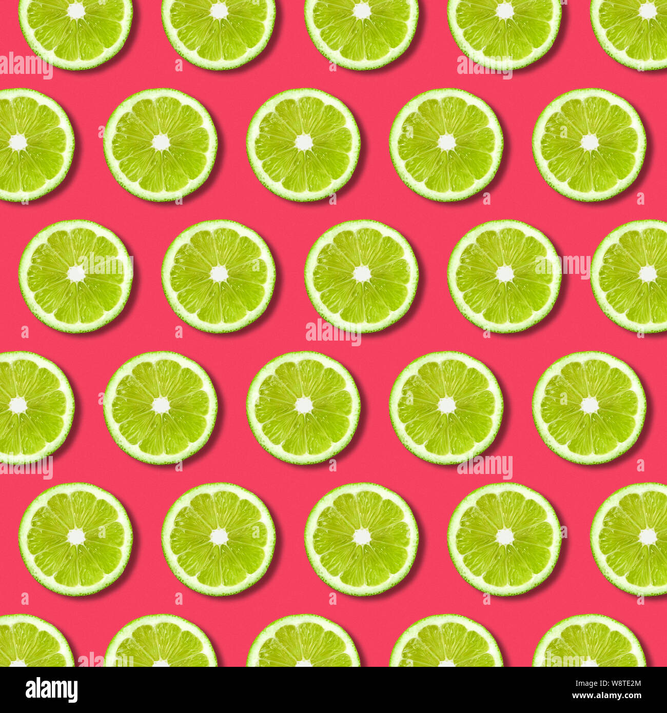 Vibrant fruit pop art background with green lime slices on red background. Minimal flat lay food pattern and texture Stock Photo