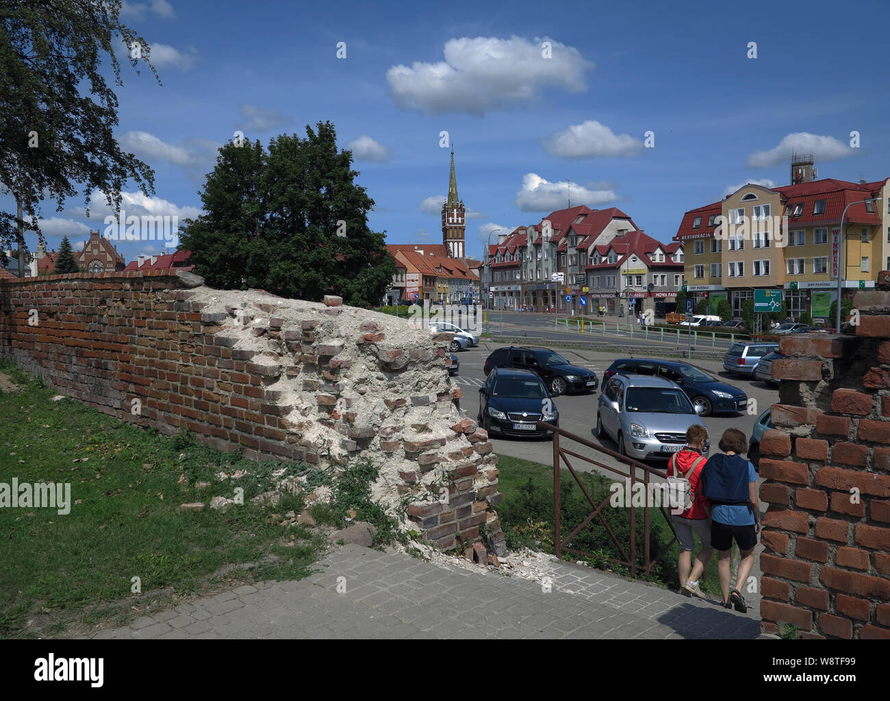 View on remnants of the old city wall and citizen houses in the town Ketrzyn (Rastenburg) in the polish Masuria (former Ostpreussen) - in the background the neo-gothic church St. Katharina, taken on 15.07.2019 | usage worldwide Stock Photo
