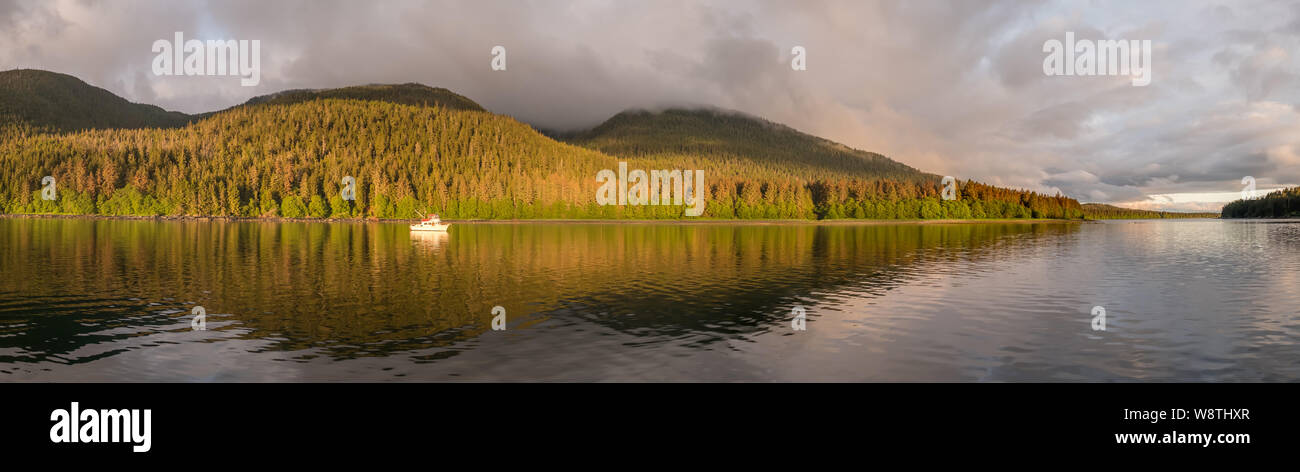 Motorboat Moored in Calm Water in the Evening at Cleveland Passage Between Whitney Island  and the Fanshaw Range on Mainland North America, Alaska USA Stock Photo