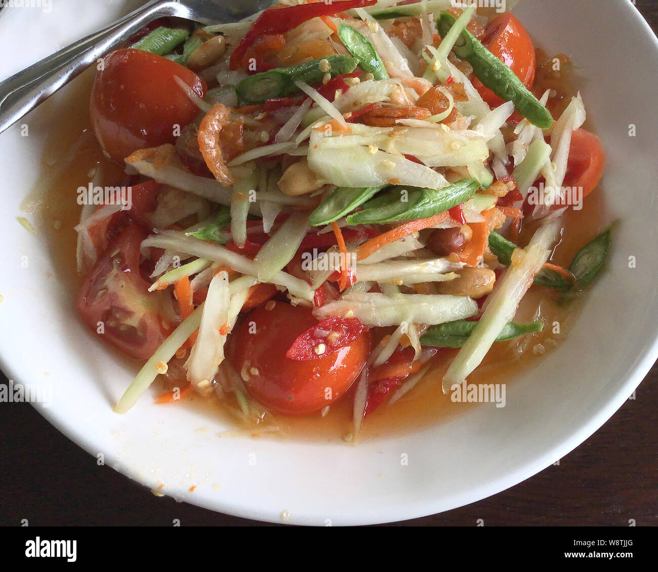 Close Up On Thai Papaya Salad On White Plate Over Wooden