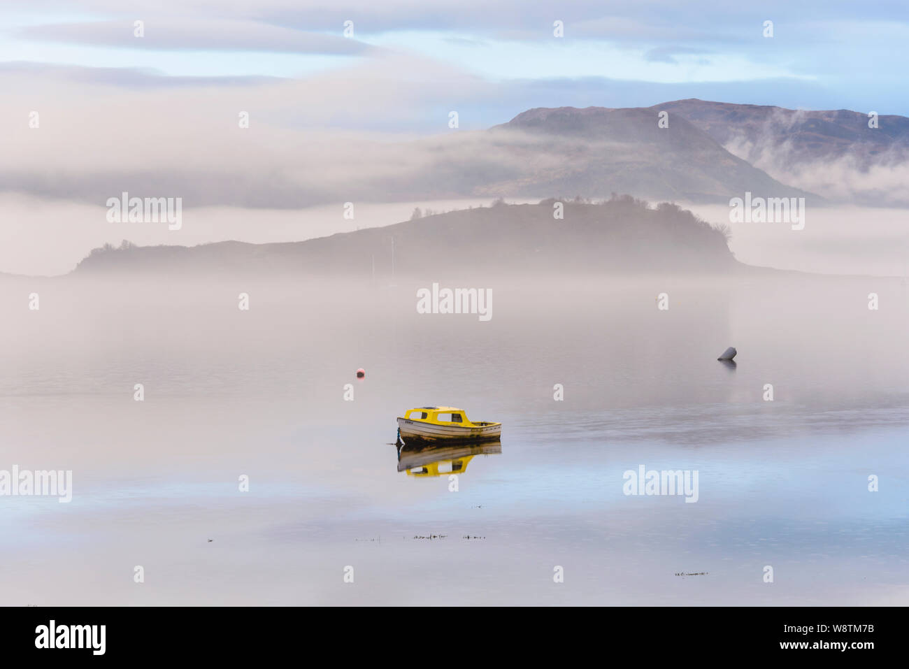 Small boat in mist and fog on Loch Carron, Wester Ross, Highlands of Scotland Stock Photo