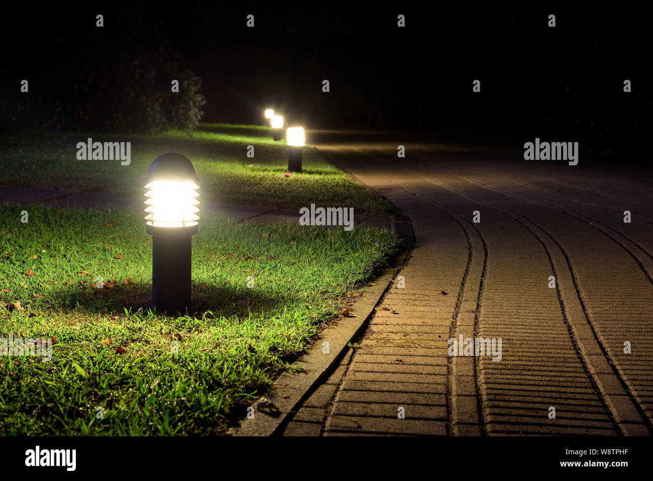 Alley illuminated by the garden lamps in the night Stock Photo
