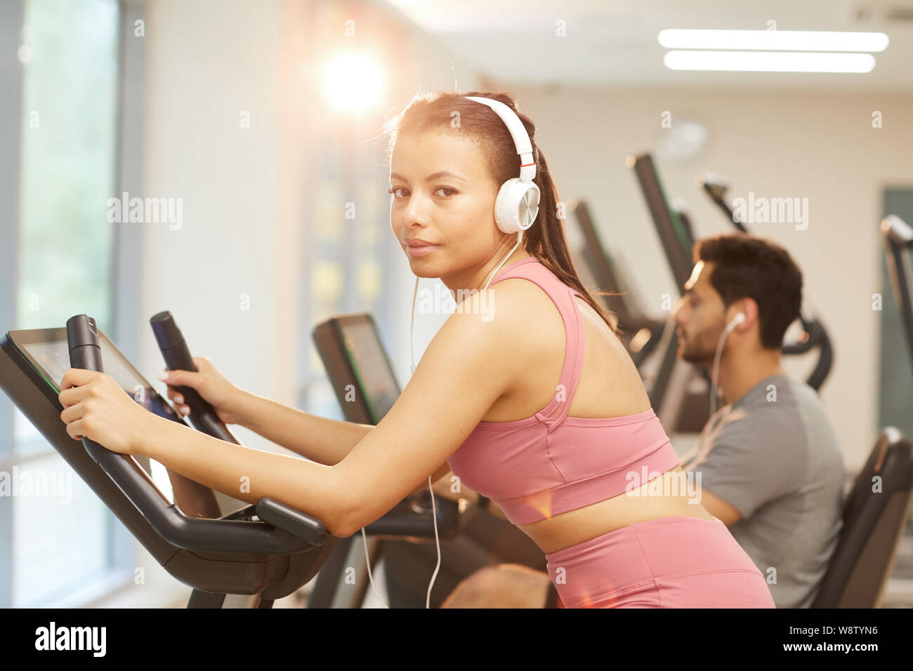 Waist up portrait of young woman wearing headphones looking at camera while exercising in gym, copy space Stock Photo