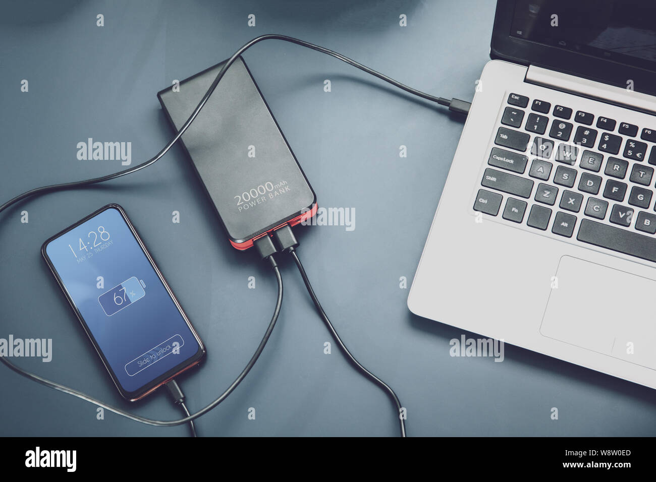 Powerfull power bank charges two devices at one time via USB-C connection. Interface on the screen was created in graphic program. Stock Photo