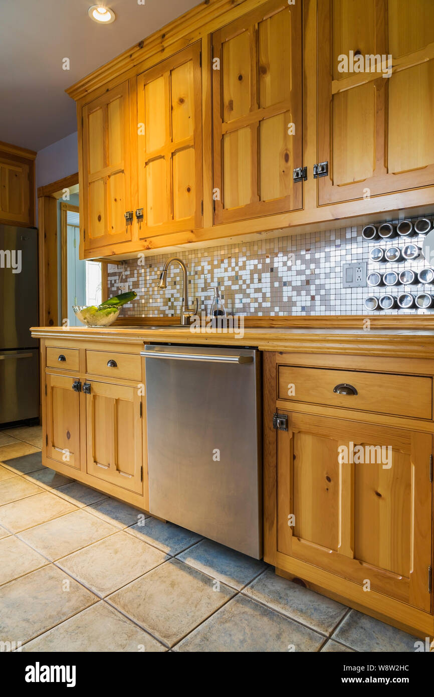 Pinewood cabinets and stainless steel dishwater in kitchen ...