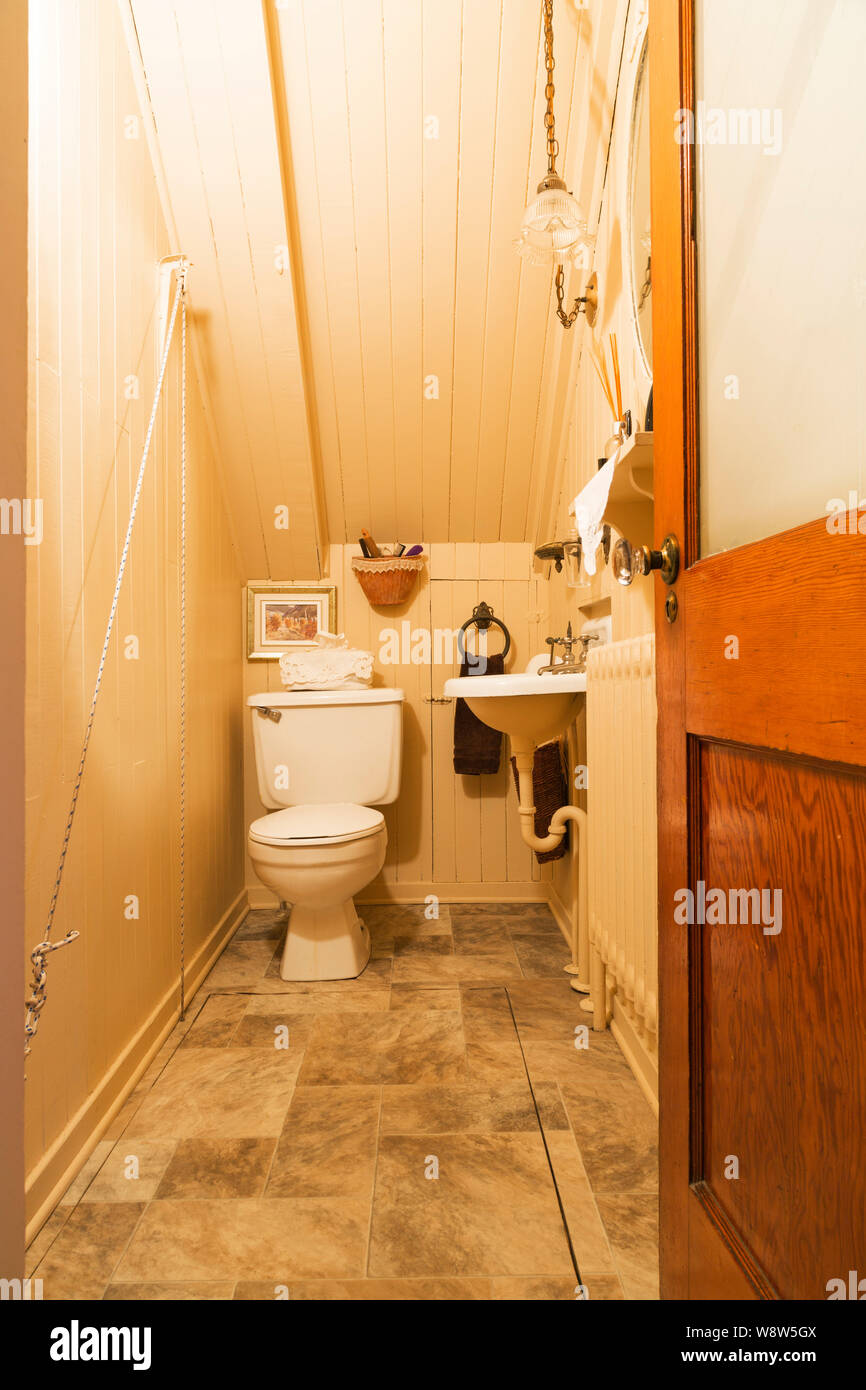 Water closet with white toilet and sink inside an old 1927 American Four Squares house Stock Photo