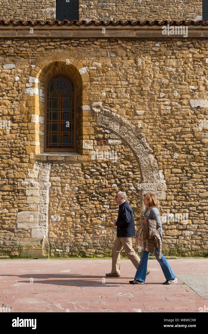 A couple walks by the Church of Saint Thyrsus in the Plaza de Alfonso II El Casto in Oviedo, Spain. The Asturian capital of Oviedo is the traditional Stock Photo