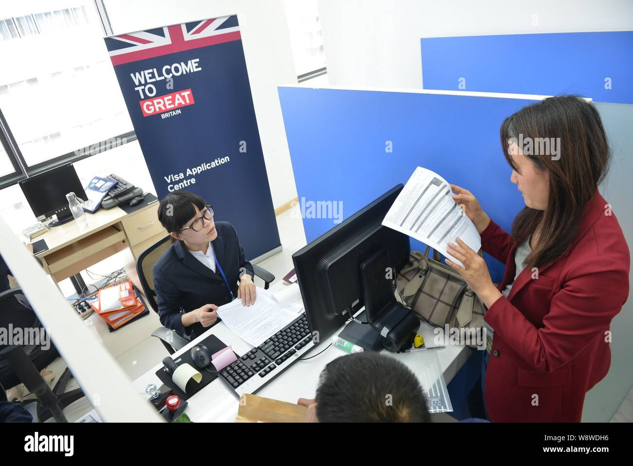 FILE--A Chinese employee serves applicants at the UK Visa