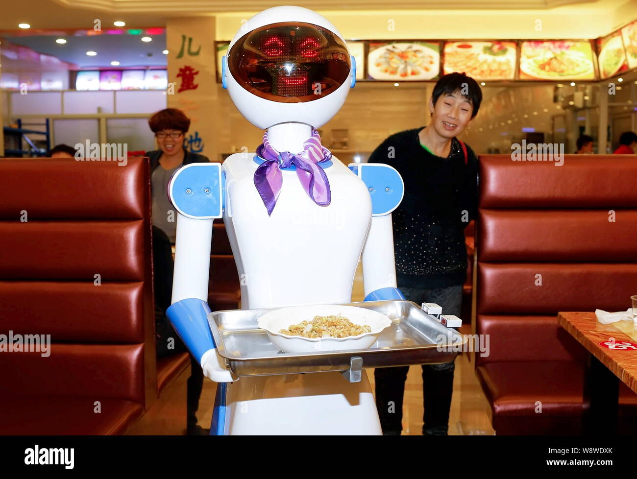 Customers look at a robot waiter at a restaurant in Cixi