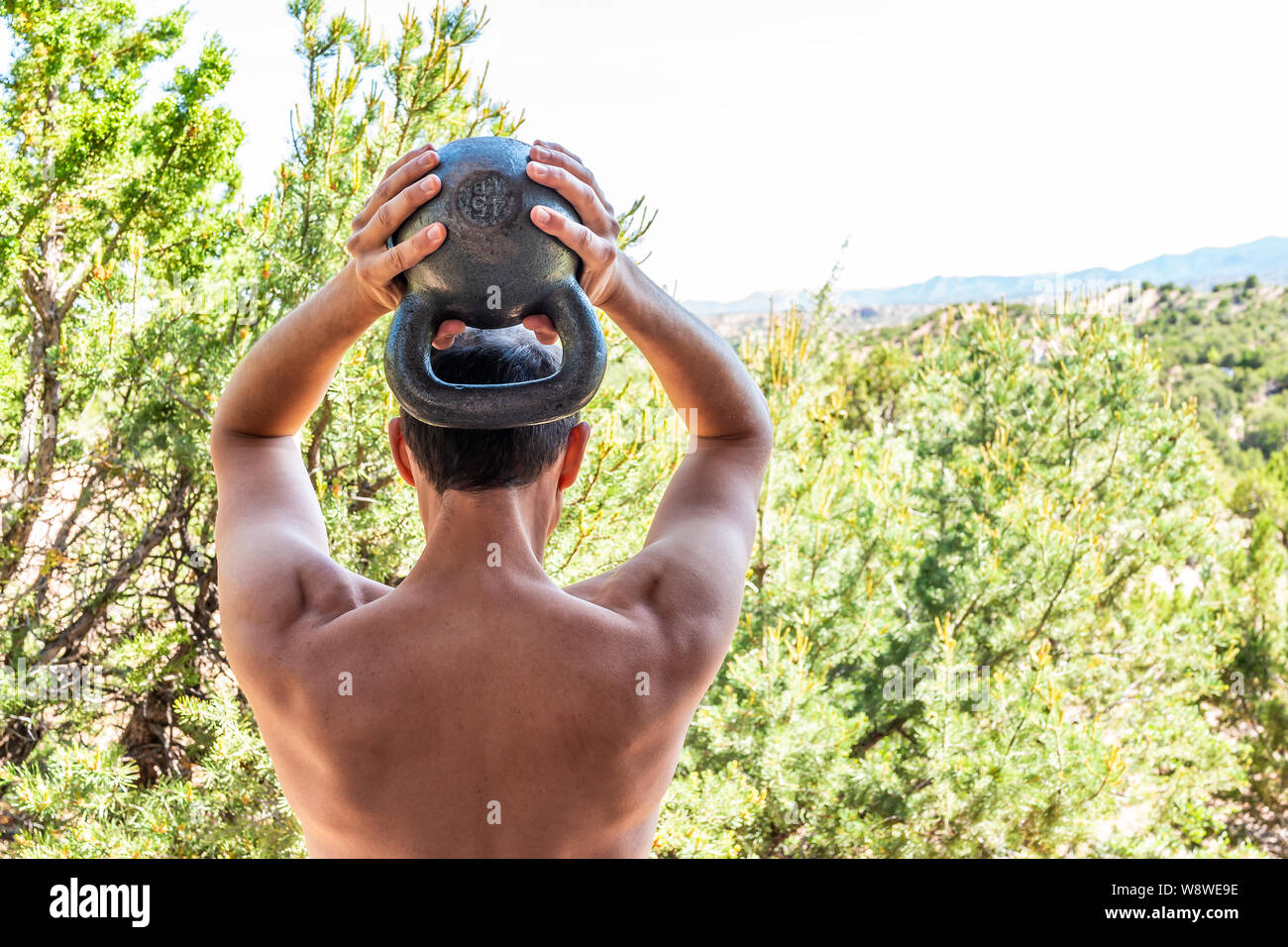 Back of young fit shirtless man with heavy kettlebell doing triceps exercise and muscles in outdoors outside park holding weight lifting Stock Photo