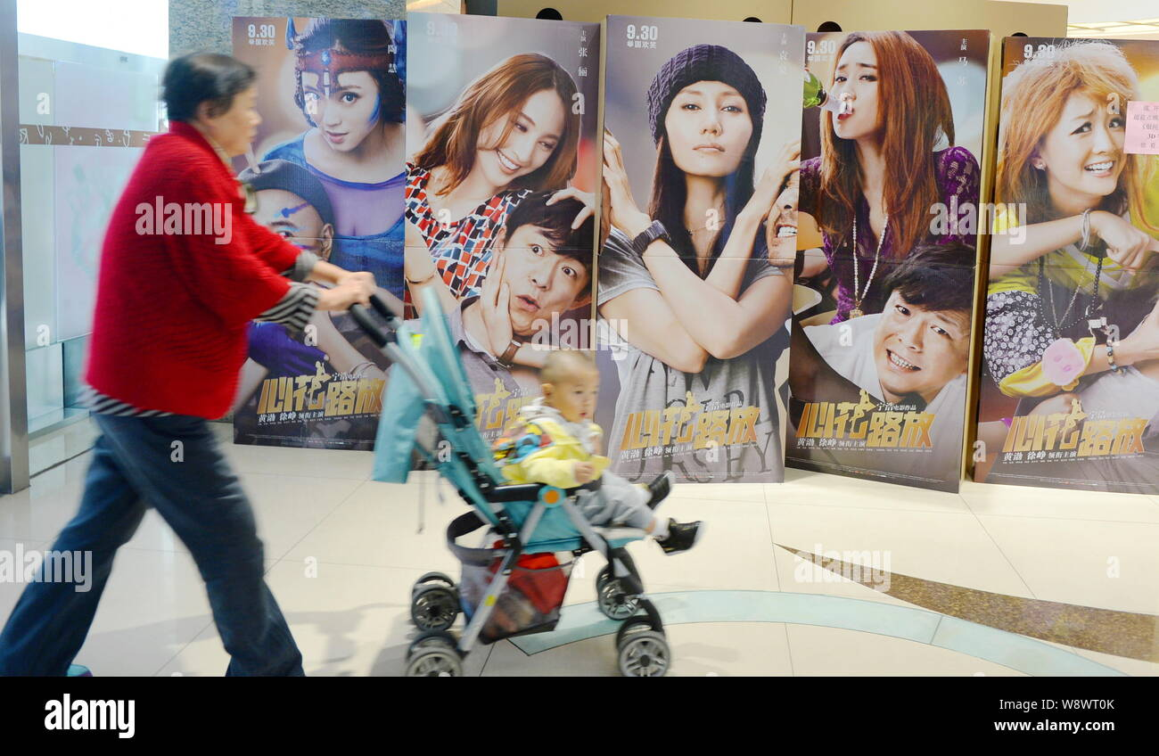 An Elder Woman Pushes A Baby Stroller Past Posters Of The Movie Breakup Buddies At A Cinema In Beijing China 8 October 2014 The Road Comedy Br Stock Photo Alamy