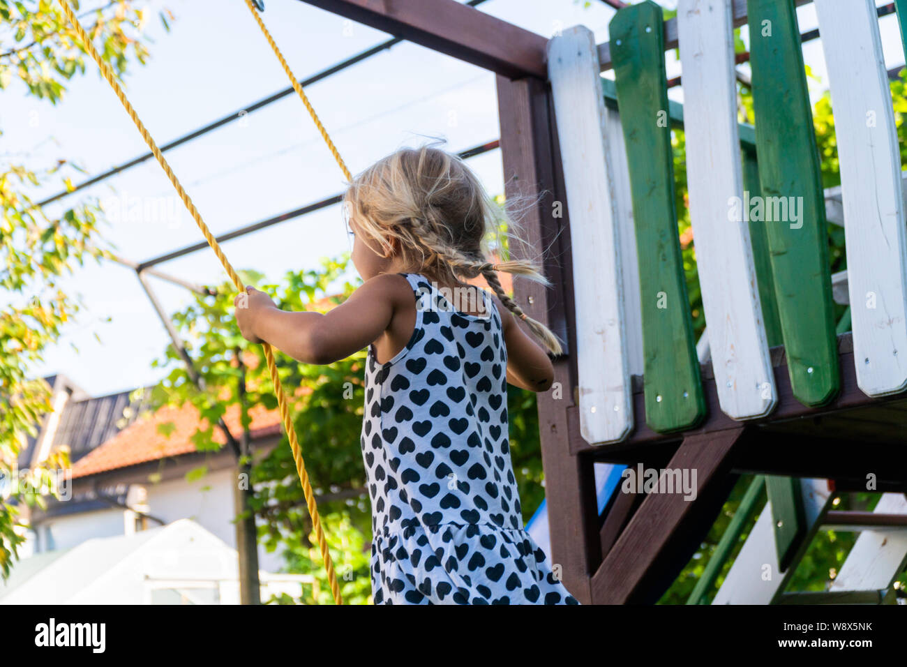3-5 year old blond girl having fun on a swing outdoor. Summer playground. Girl swinging high. Young child on swing in garden Stock Photo