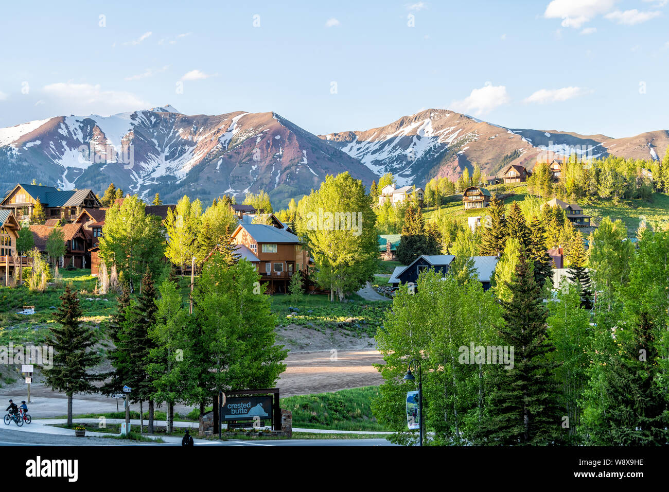 Mount Crested Butte, USA - June 21, 2019: Colorado village in summer with colorful sunset by houses on hills with green trees and main street road Stock Photo