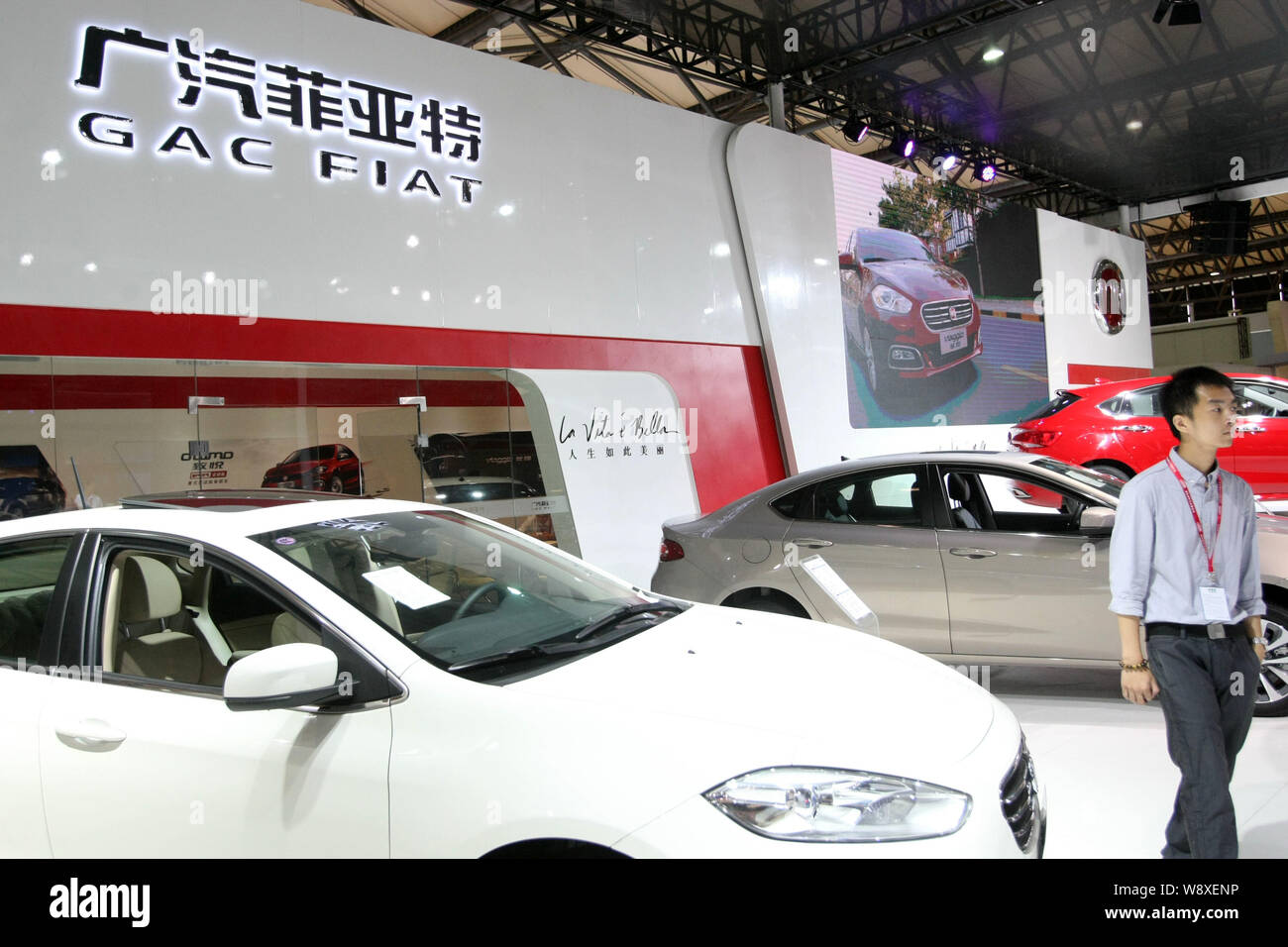 --FILE--A Chinese employee walks past a car at the stand of GAC Fiat Chrysler, a joint venture between Guangzhou Automobile Group Co (GAC) and Fiat Ch Stock Photo