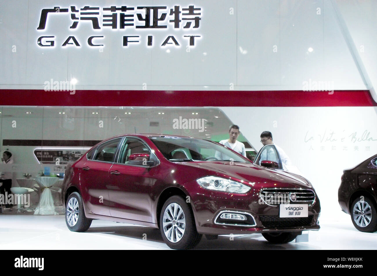 --FILE--Visitors look at a Fiat Viaggio at the stand of GAC Fiat Chrysler, a joint venture between Guangzhou Automobile Group Co (GAC) and Fiat Chrysl Stock Photo
