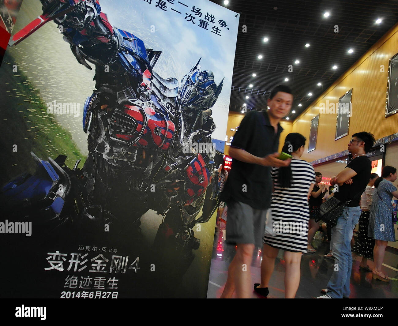 Moviegoers stand next to a poster of the movie, Transformers