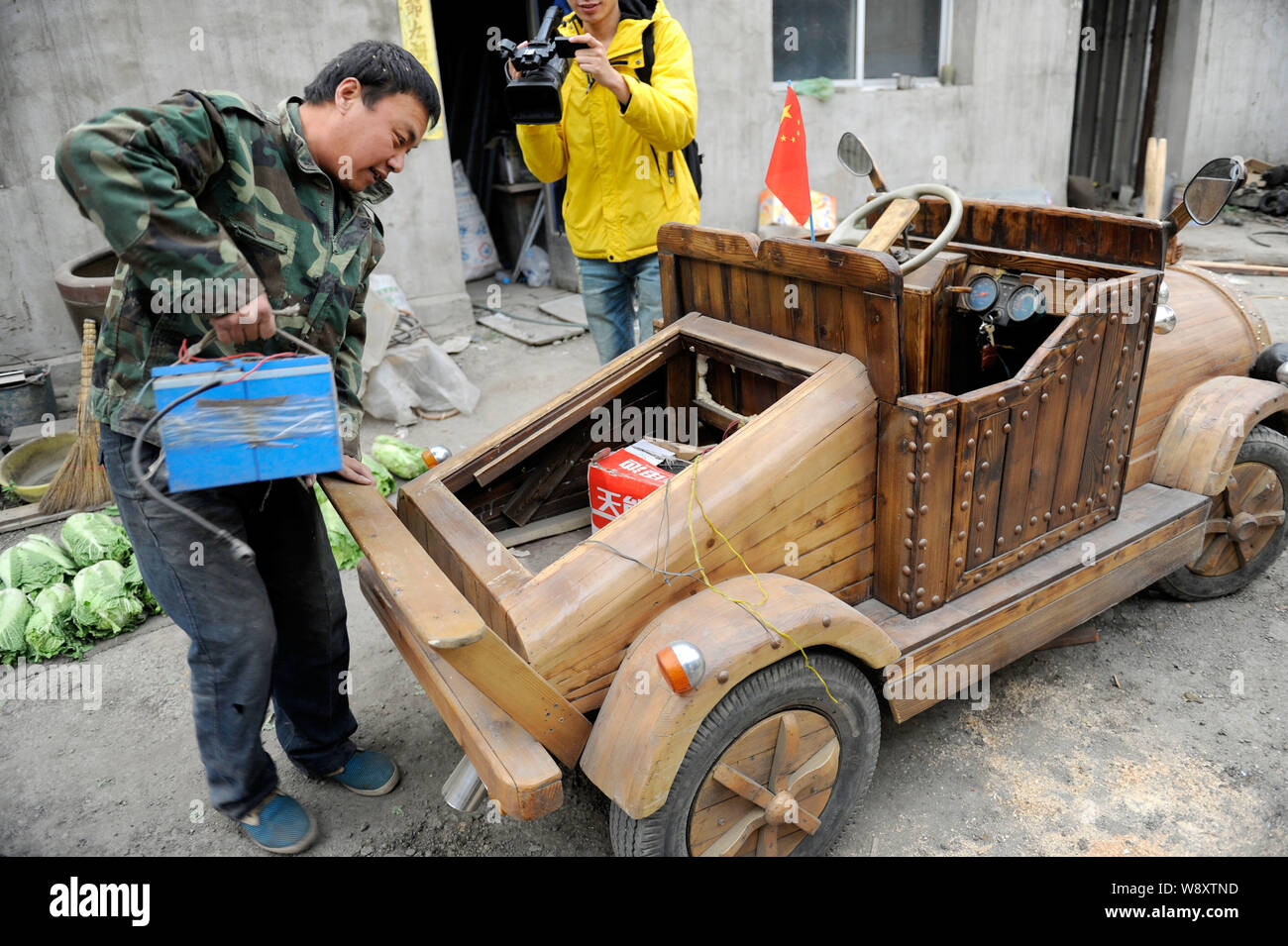 Chinese Carpenter Liu Fulong Puts A Recharged Storage Battery Into