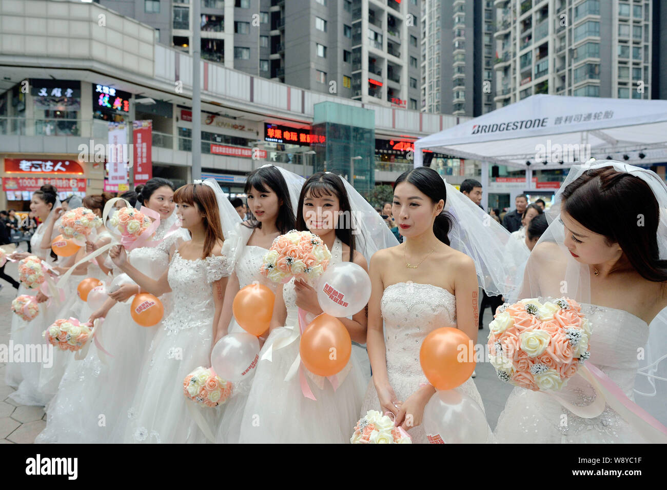 Single Women Dressed In Wedding Gowns Hold Bouquets Of Flowers And