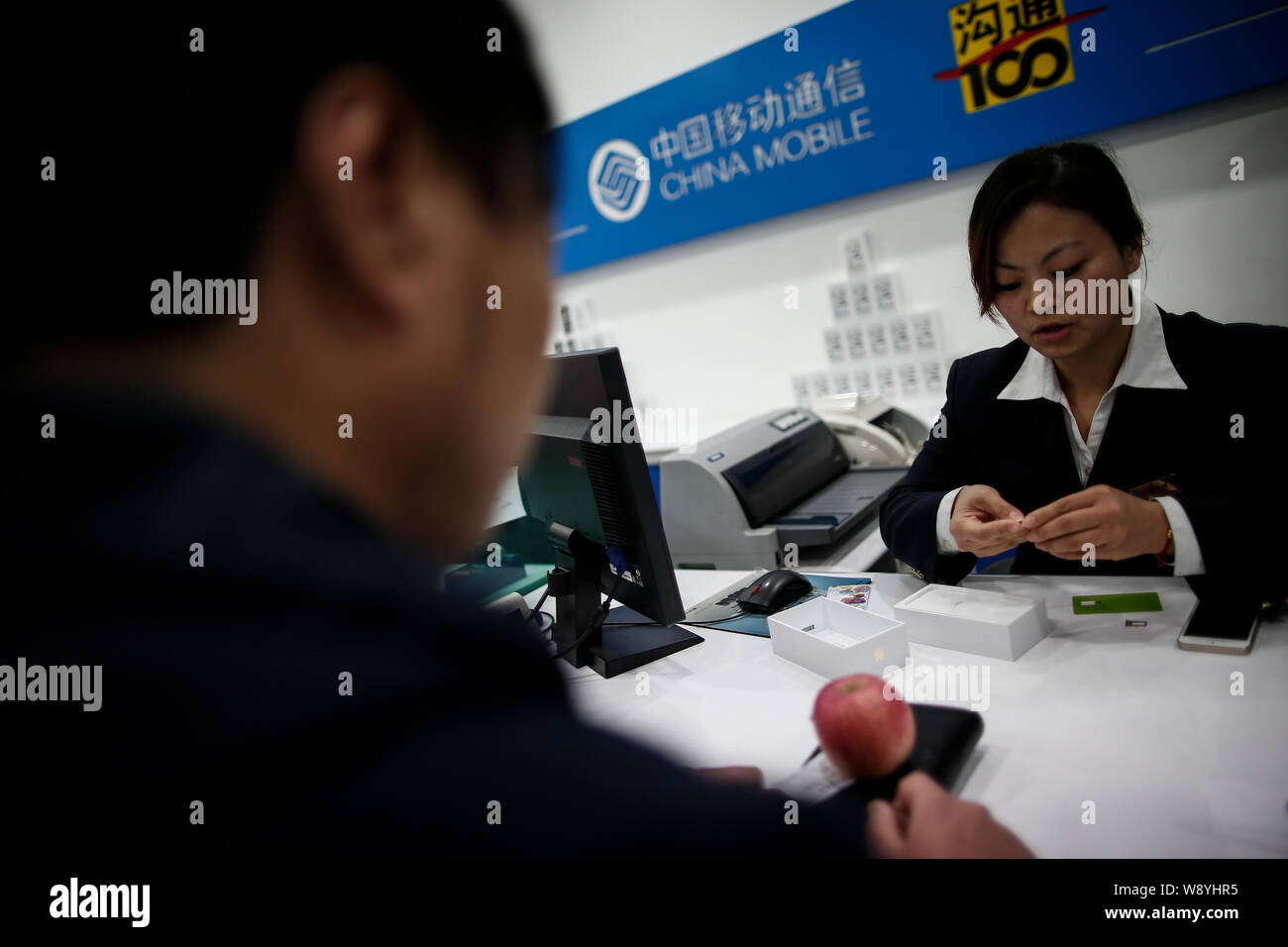 A Chinese employee prepares a nano-SIM card for a buyer of