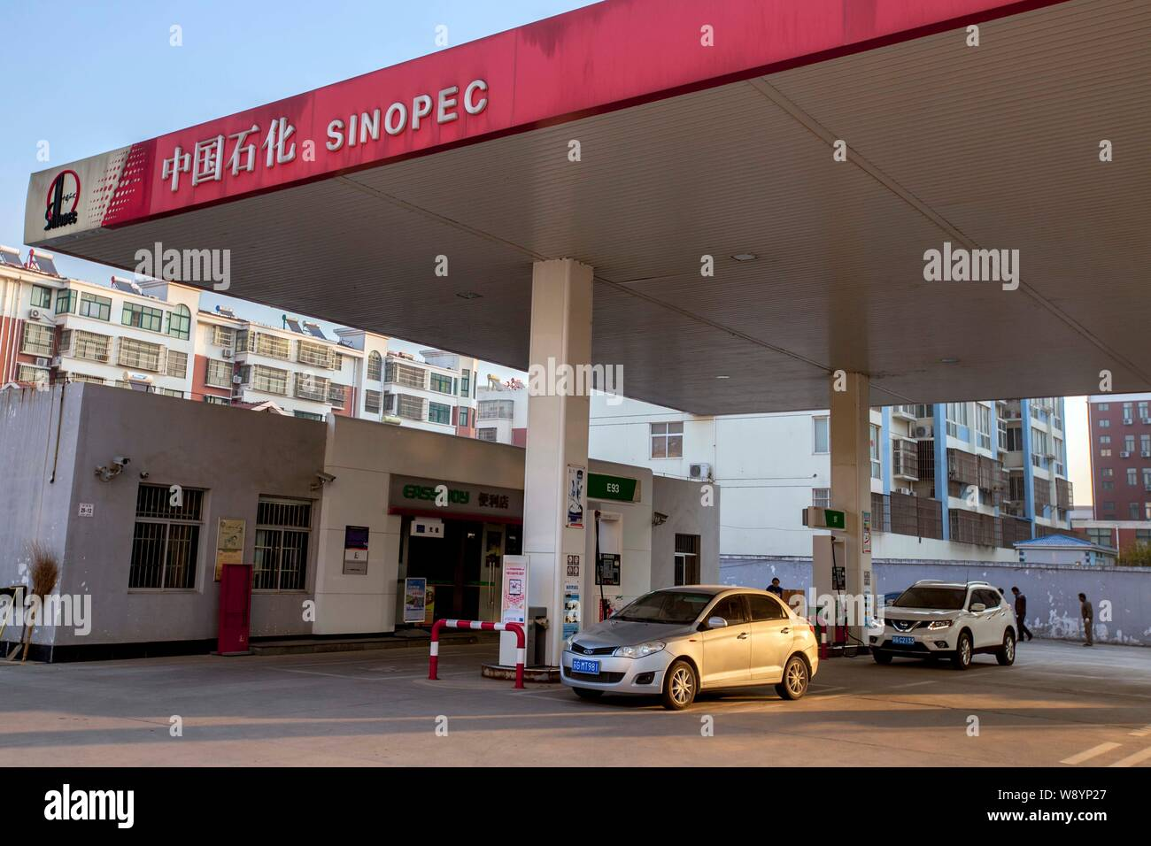 Vehicles are being refueled at a gas station of Sinopec in Lianyungang city, east Chinas Jiangsu province, 14 November 2014.   Two short crude oil pip Stock Photo