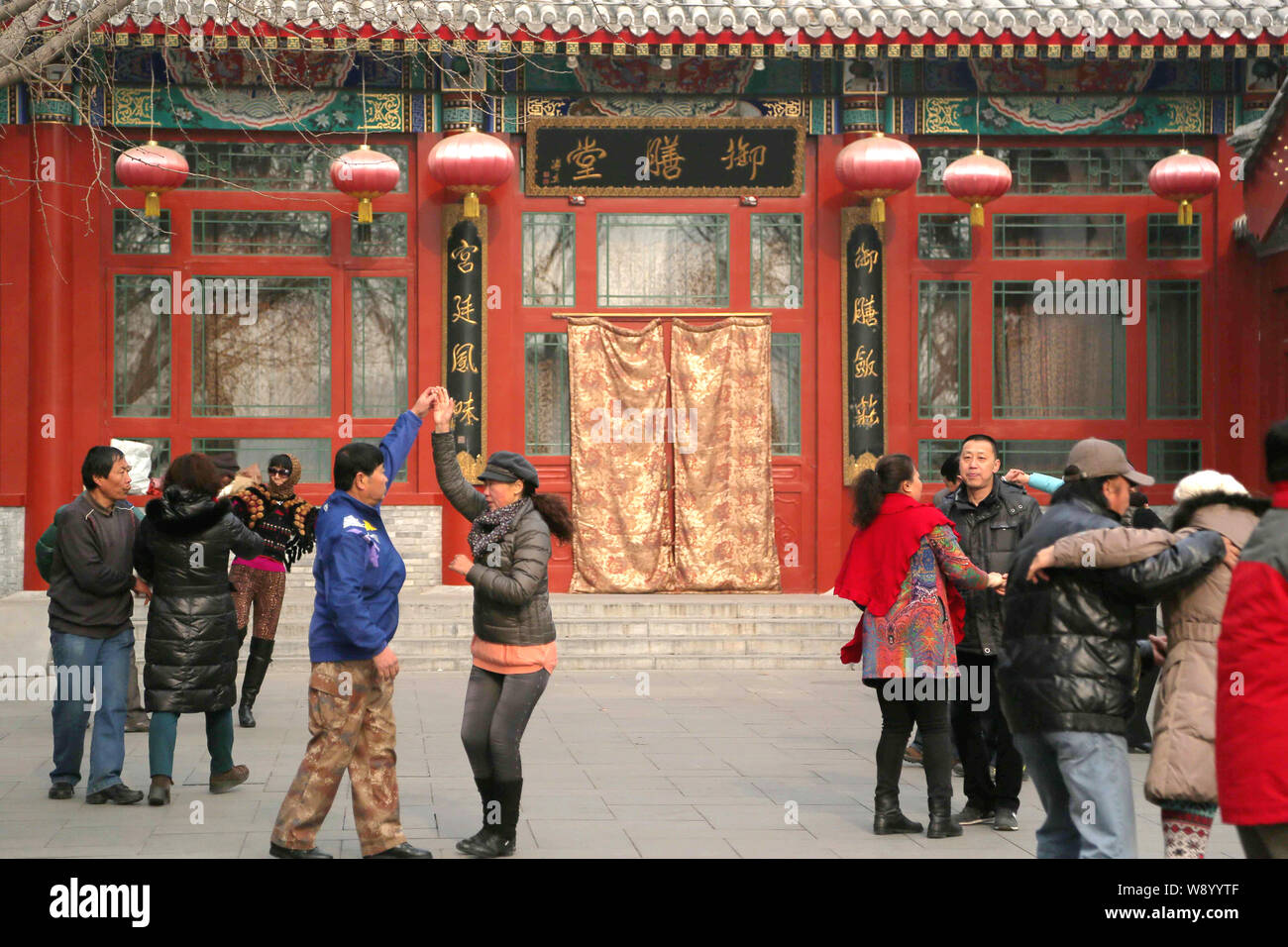 People dance in front of the closed Imperial Court Club, also known as Yushantang operated by high-end restaurant chain Yi Shi Liu, at Beihai Park in Stock Photo
