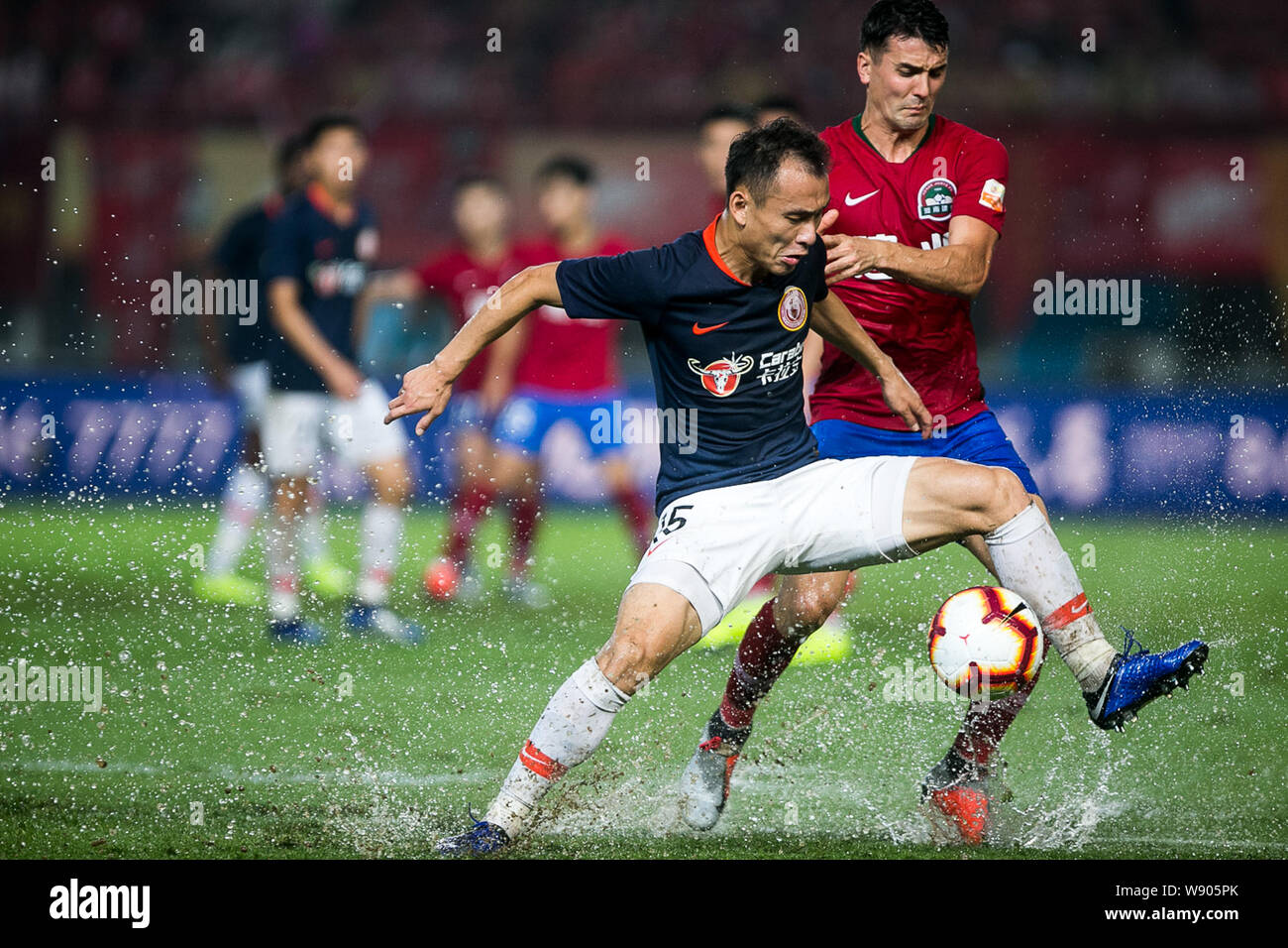 English-born Taiwanese football player Tim Chow, right, of Henan Jianye challenges a player of Beijing Renhe in their 23rd round match during the 2019 Chinese Football Association Super League (CSL) in Zhengzhou city, central China's Henan province, 9 August 2019. Henan Jianye defeated Beijing Renhe 2-1. Stock Photo