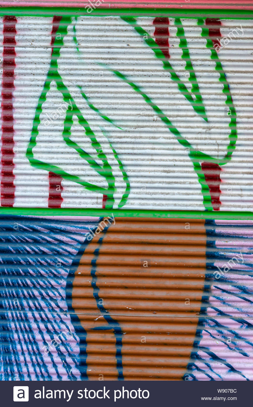 Colorful painted graffiti on a corrugated metal fence Stock