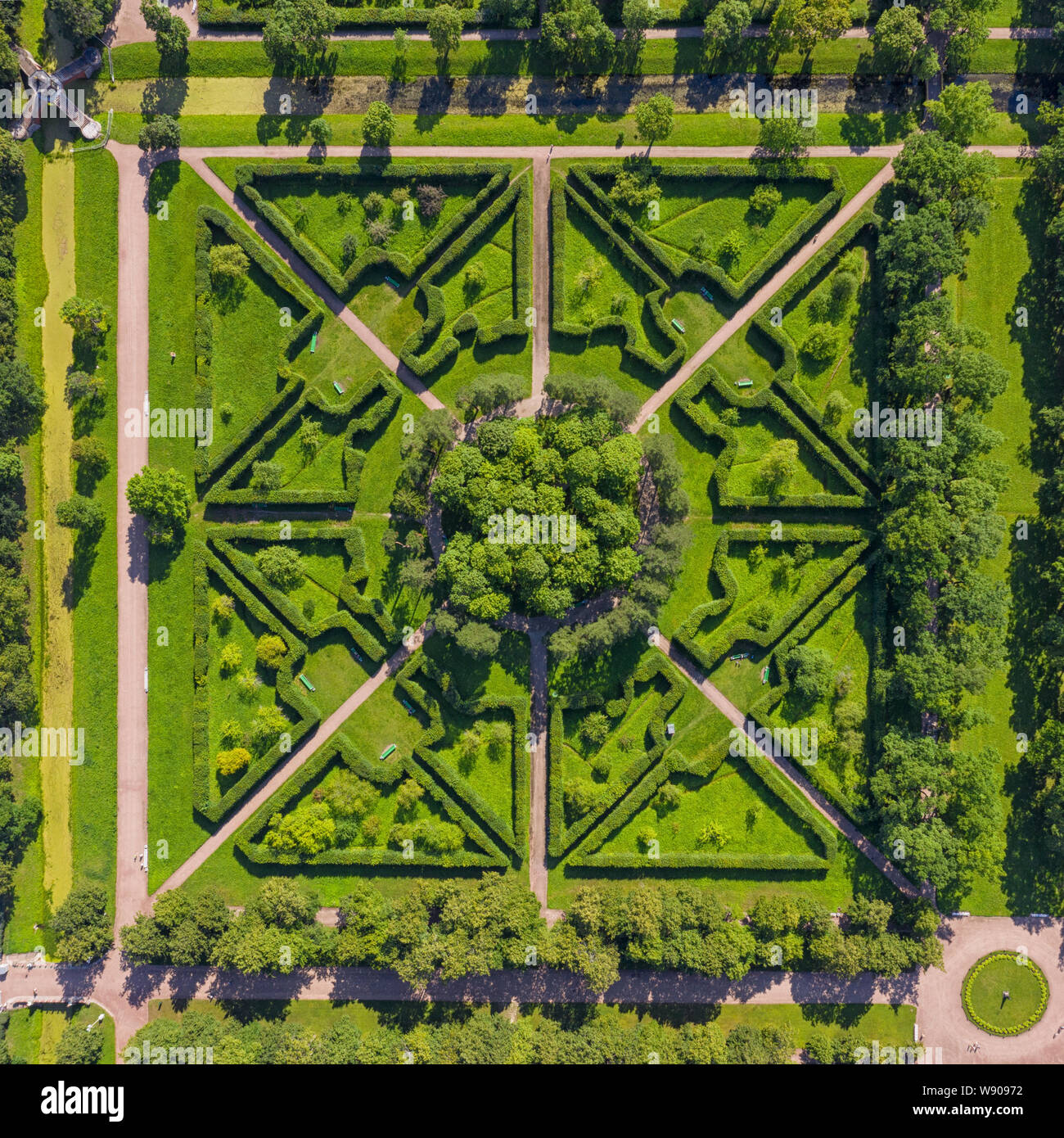 Square fragment of green formal garden aerial top view at sunny day. Stock Photo