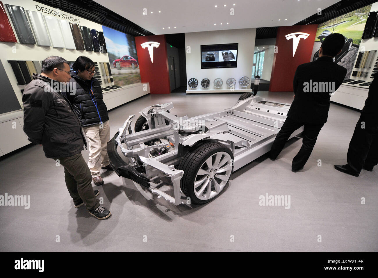 Visitors look at a chassis of the Model S on display at the Tesla store in Beijing, China, 5 November 2013.   US electric carmaker Tesla Motors opened Stock Photo