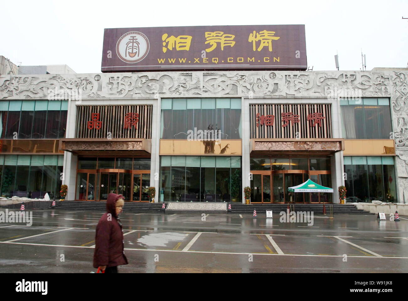 --FILE--A pedestrian walks past a Xiang E Qing restaurant in Wuhan city, central Chinas Hubei province, 1 March 2013.   Chinas high-end restaurants ha Stock Photo