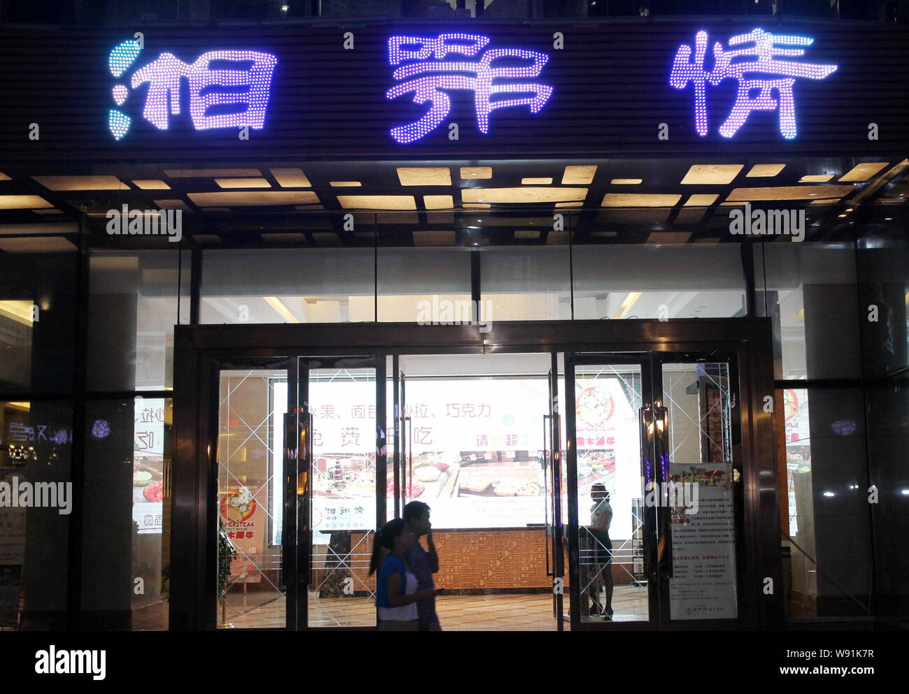 --FILE--Pedestrians walk past a Xiang E Qing restaurant in Wuhan city, central Chinas Hubei province, 3 August 2013.   Chinas high-end restaurants hav Stock Photo