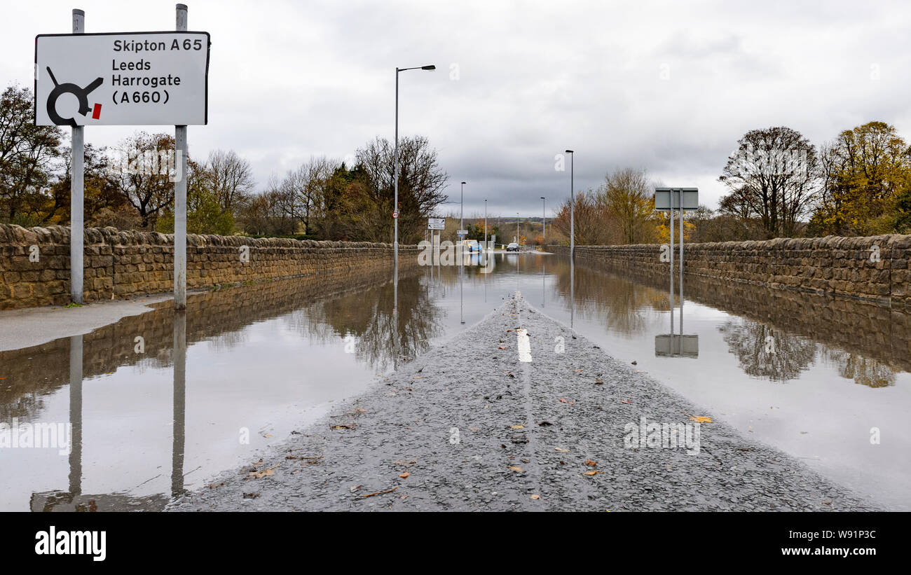 Flooding - flooded road (closed to cars) with trees & signs reflected in standing flood water - Burley In Wharfedale, Yorkshire, England, UK. Stock Photo