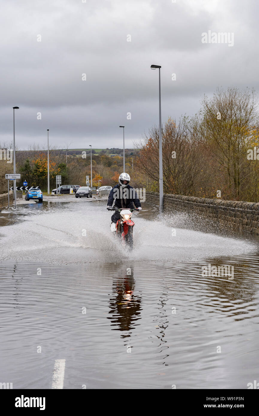 Flooding - motorcyclist riding (splashing) motorbike in flood water on flooded road, impassable to cars - Burley In Wharfedale, Yorkshire, England, UK Stock Photo