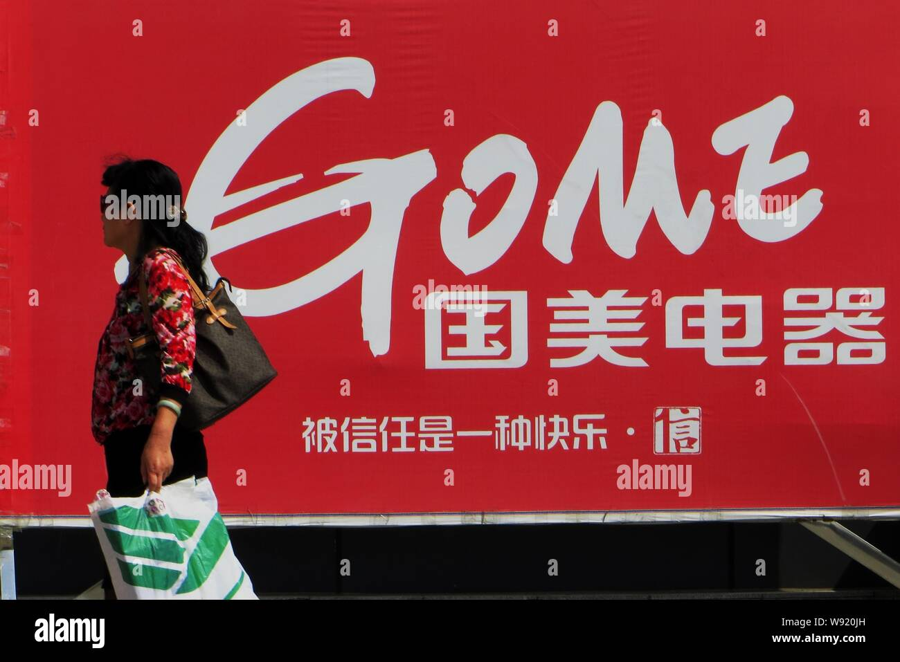 --FILE--A pedestrian walks past an advertisement for Gome Electrical Appliances in Yichang, central Chinas Hubei province, 10 October 2013.   Chinese Stock Photo