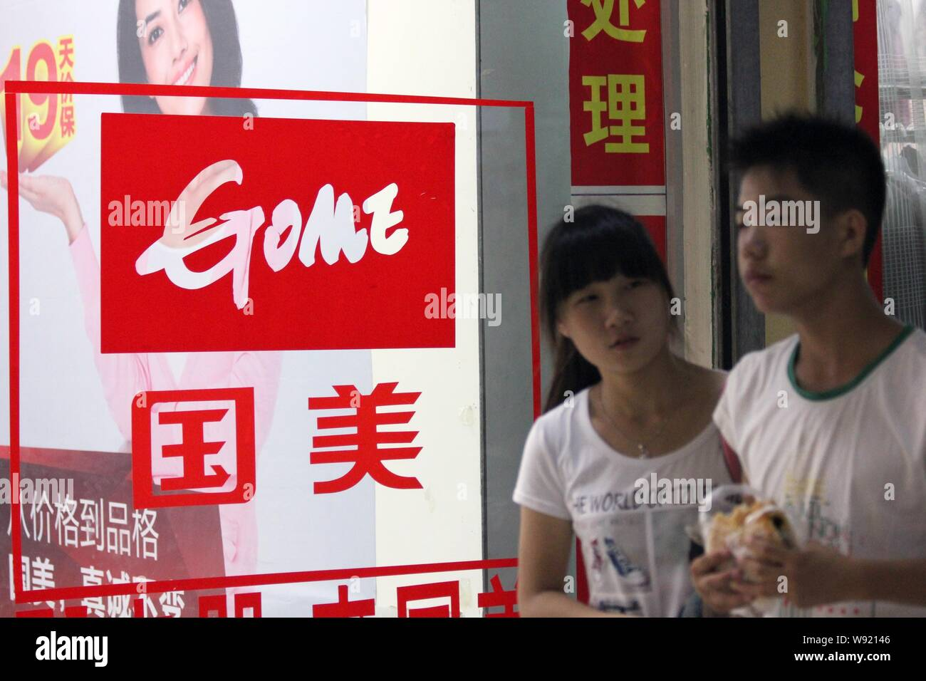 --FILE--Pedestrians walk past an advertisement for Gome Electrical Appliances in Zhoukou, central Chinas Henan province, 16 August 2013.   Chinese Bes Stock Photo