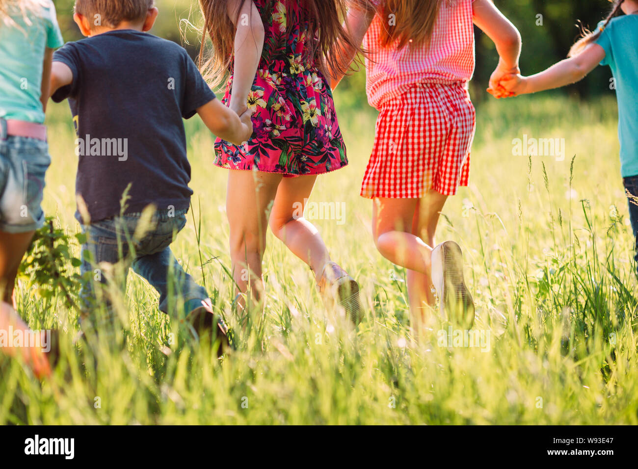 Large group of kids, friends boys and girls running in the park on sunny summer day in casual clothes . Stock Photo