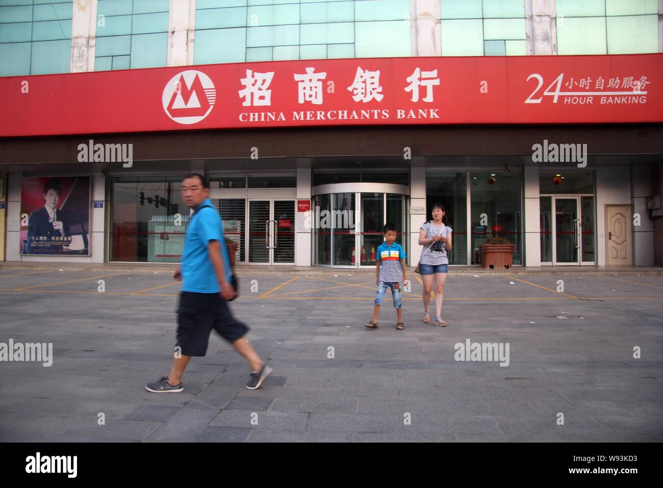 --FILE--Pedestrians walk past a branch of China Merchants Bank (CMB) in Qingdao, east Chinas Shandong province, 7 August 2013.   JPMorgan Chase & Co. Stock Photo