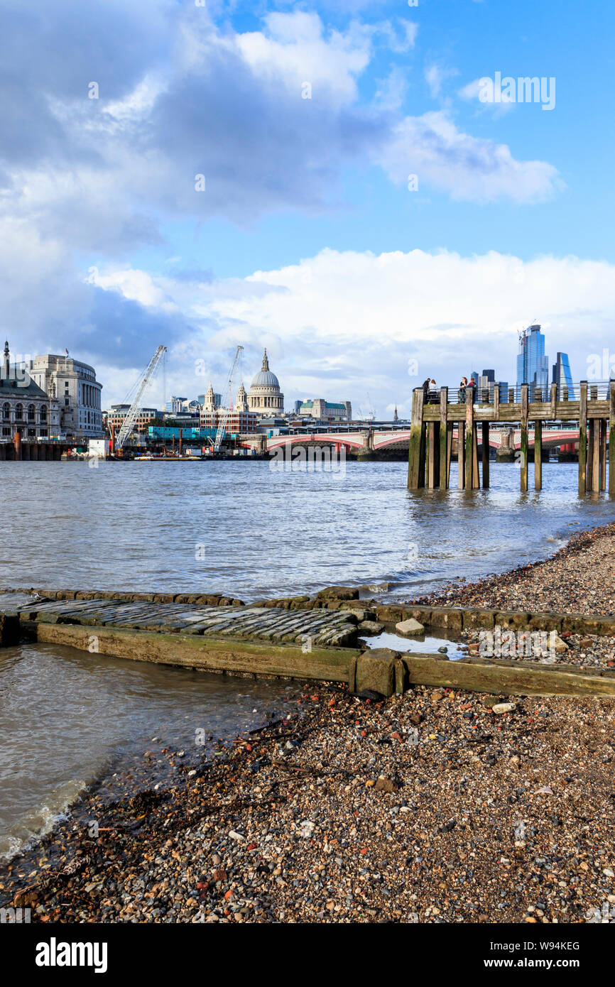 View from the River Thames at low tide, St Paul's Cathedral and the City in the distance, a Victorian slipway in the foreground, London, UK Stock Photo