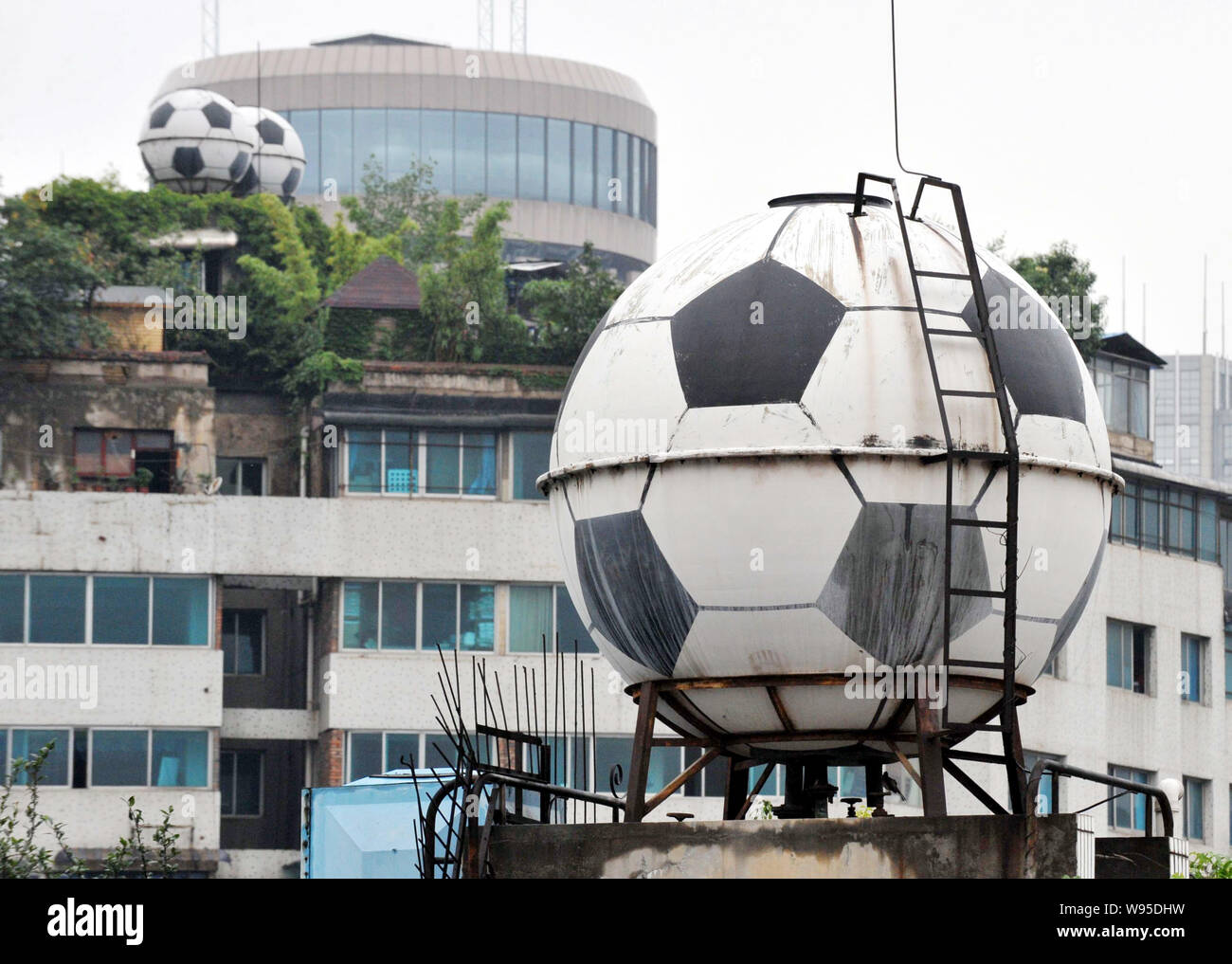 Football-shaped water tanks supplying tap water are pictured on the rooftop of residential apartment buildings in Guiyang city, southwest Chinas Guizh Stock Photo