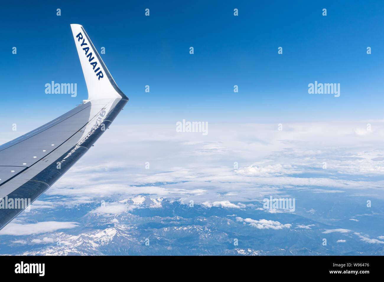 Austria - 07 July, 2019: Flight Palma de Mallorca, Spain - Krakow, Poland. Ryanair airplane wing on sky background. Above the Alps mountains. Stock Photo