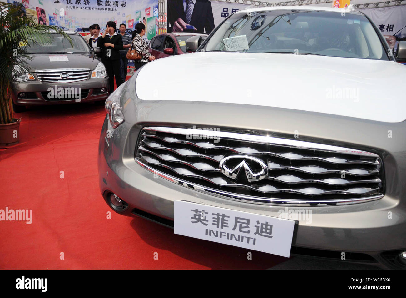 Visitors look at Nissan and Infiniti cars during an auto show in Binzhou city, east Chinas Shandong province, 22 April 2012.   Luxury automaker Infini Stock Photo