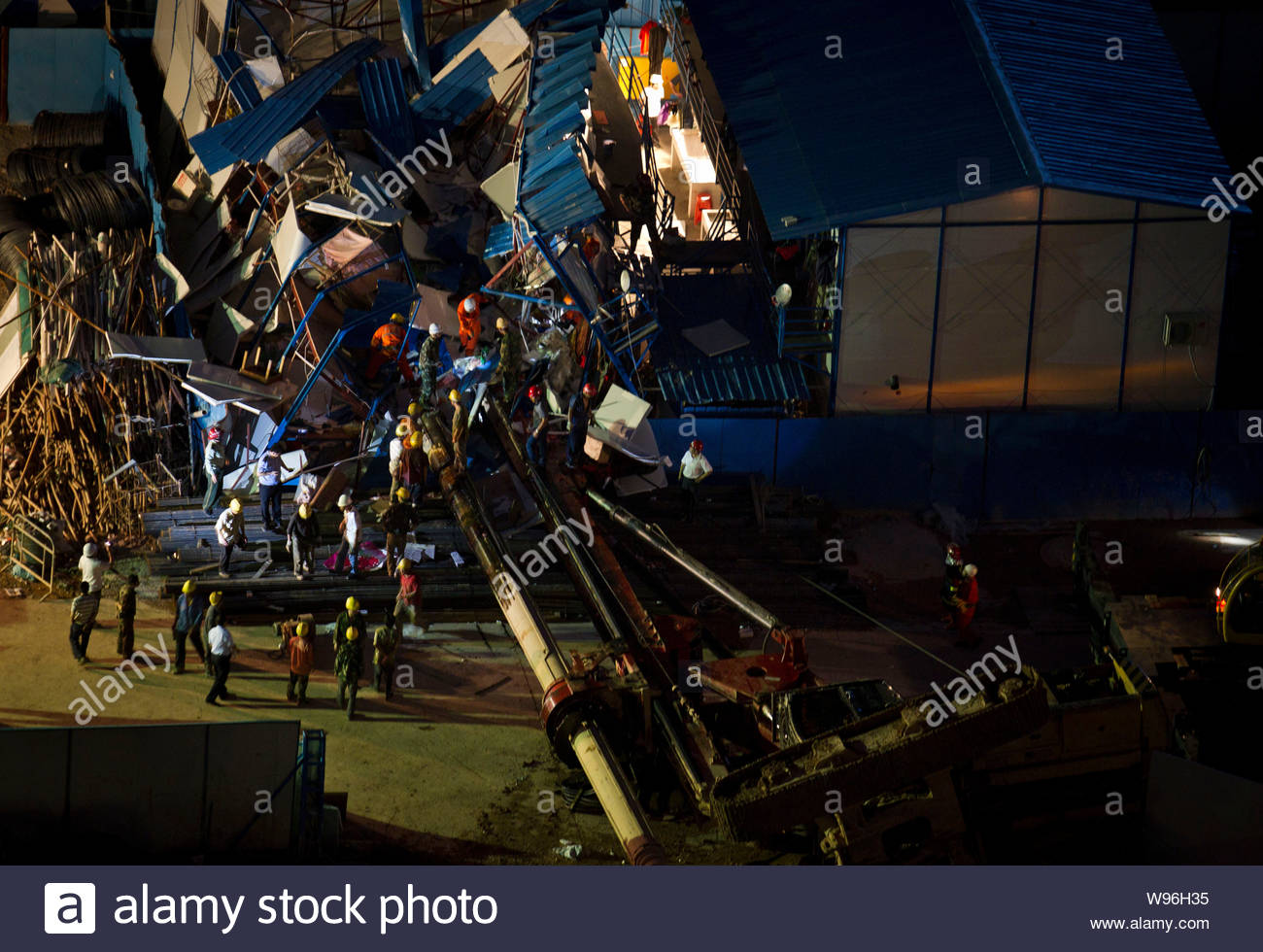 Rescuers are seen at the accident site where a pile driver toppled over and destroyed a shed in Shenzhen, south Chinas Guangdong province, 14 April 20 Stock Photo