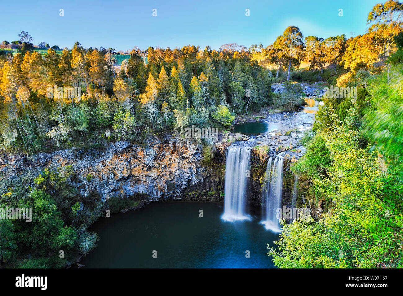 Elevated view over Dangar falls in Dorrigo National park near Dorrigo town in morning soft light with smooth water stream falling down to rock pool cu Stock Photo