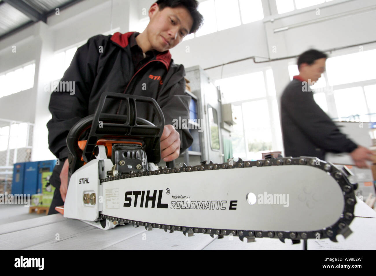 A Chinese worker shows an electric motor saw at the plant of