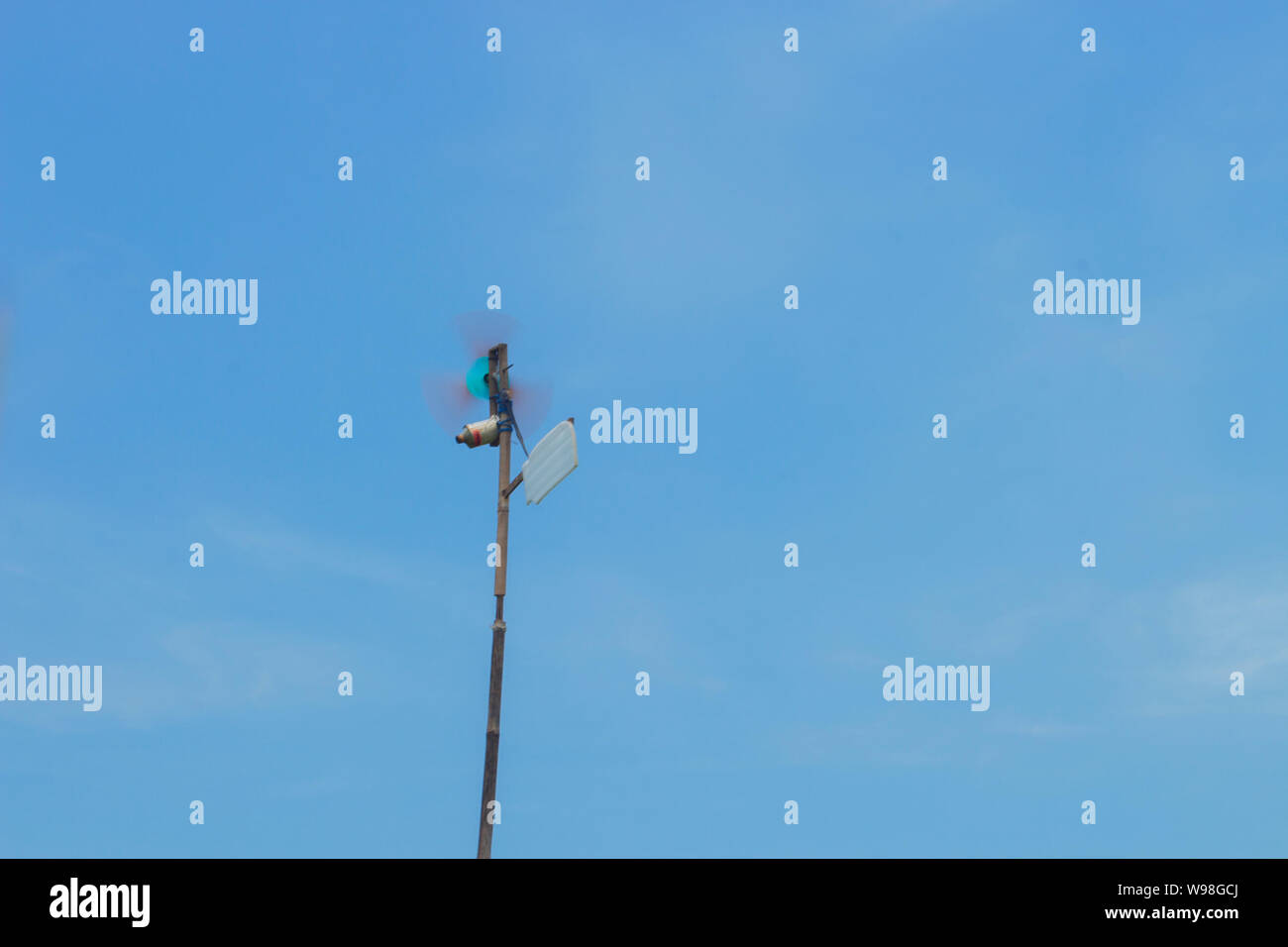 Traditional Windmill Made From Used Can Spinning on The Blue Sky in Rice Field in Indonesia Stock Photo