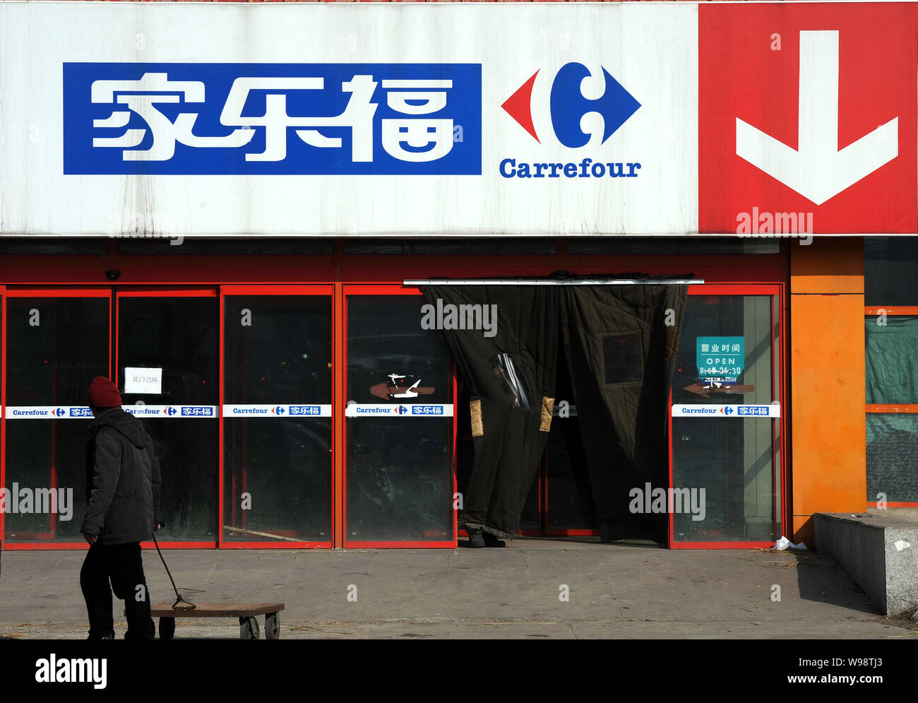 FILE--A worker pulls a cart past a closed Carrefour