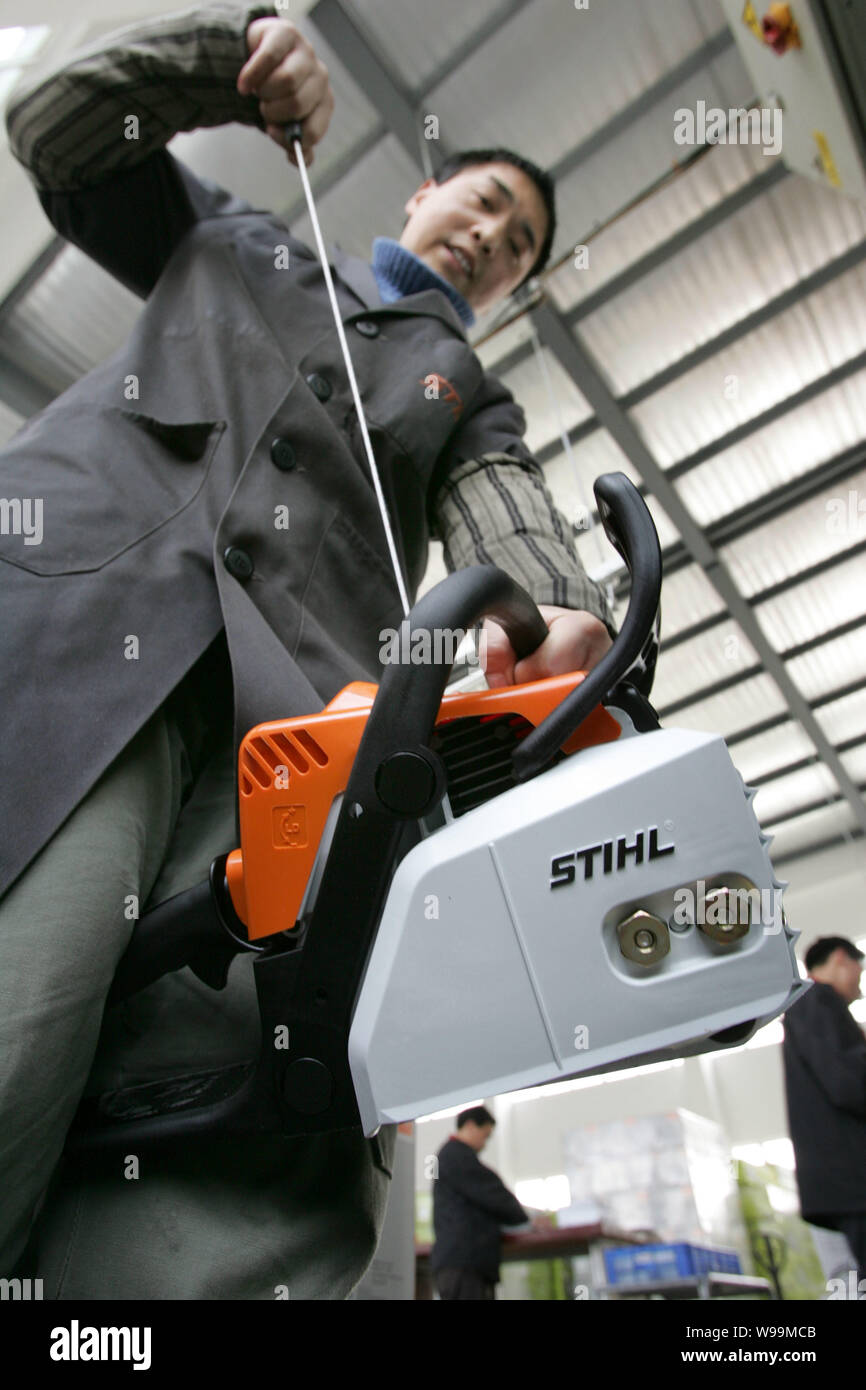 A Chinese worker starts an electric motor saw in a warehouse