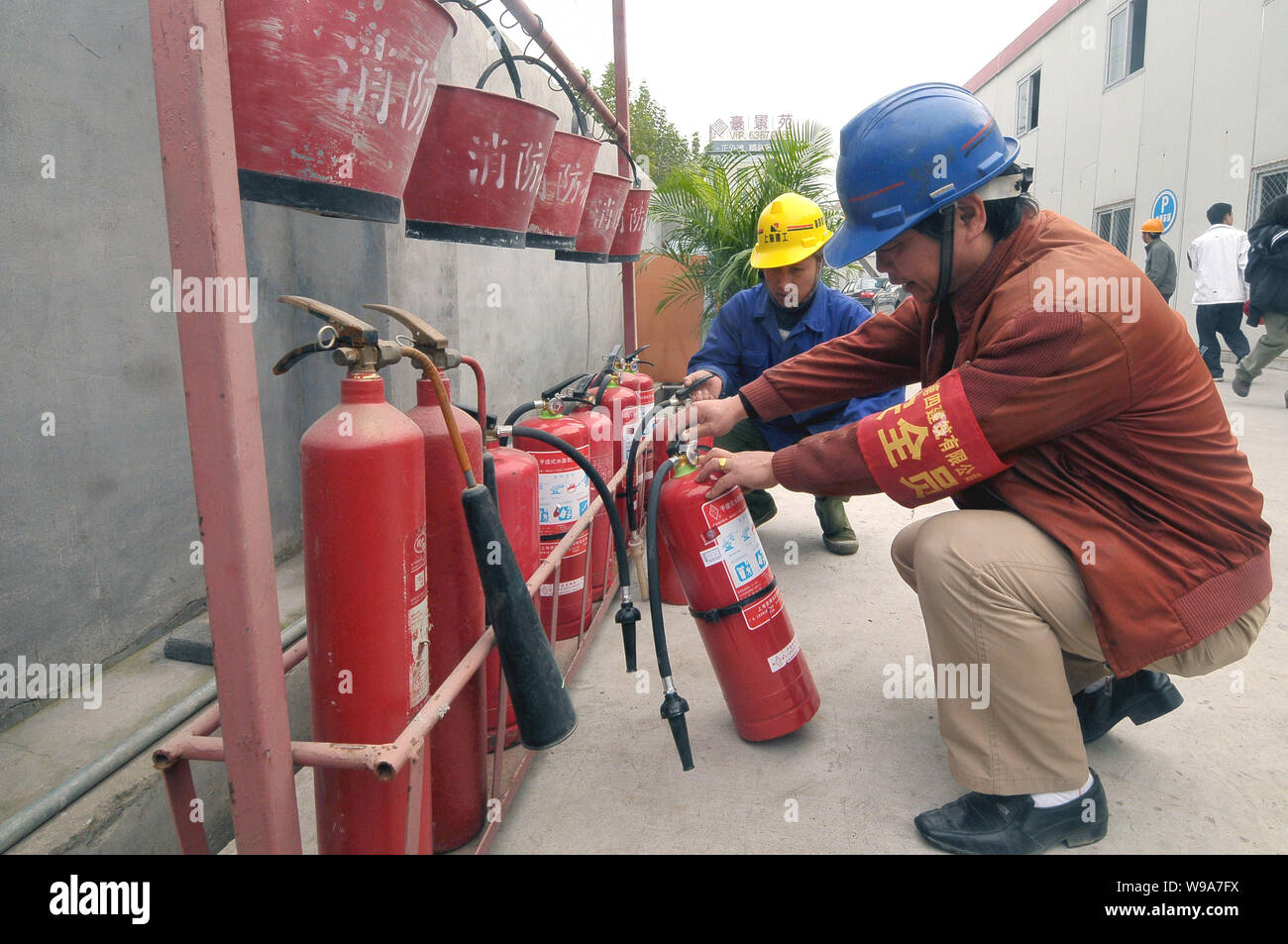 Chinese workers check the fire extinguishers and other